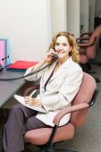 Businesswoman on phone taking notes in office workstation