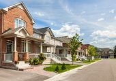 stock photo of row houses  - Suburban residential street with red brick houses - JPG