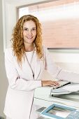 Smiling business woman operating photocopy machine in office
