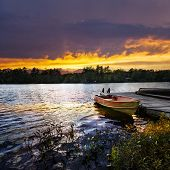 stock photo of dock a lake  - Rowboat tied to dock on beautiful lake with dramatic sunset - JPG
