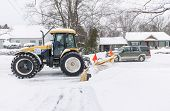 TORONTO, CANADA  FEBRUARY 5, 2014: Snowplow clears residential street after winter snowstorm on Wedn