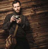 Handsome man wearing cardigan with vintage camera in wooden house interior