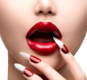 Fashion Model Girl Face. Makeup and Manicure. Red Long Nails and Red Glossy Lips. Sensual Mouth. Nail Art. Beautiful Sexy Lips. Fashion. Professional Make-up. Perfect Skin