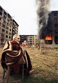 SARAJEVO, BOSNIA - MAR 18: An ethnic Croatian man prays outside his burning apartment on the last day of the Serbian siege in Sarajevo, Bosnia, on Monday, March 18, 1996.