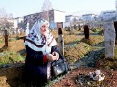 SARAJEVO, BOSNIA - MAY 29: A Bosnian Muslim woman prays over the grave of her son in a Sarajevo grav