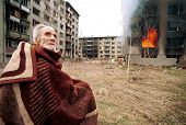 SARAJEVO, BOSNIA - MARCH 17: A Bosnian Croat man sits stunned and scared outside his burning home af
