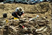 SREBRENICA, BOSNIA - JUNE 12: United Nations forensic experts unearth victims from a mass grave. The