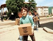 KUKES, ALBANIA, 18 APRIL 1999 --- Kosovar Albanian refugee children return to their camp in northern Albania with aid packages distributed by the United States government.