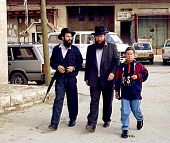 HEBRON - DECEMBER 15: Three Israeli settlers, two carrying Israeli army issued weapons, in the contested West Bank city of Hebron walk to their car from a settlements on December 15, 1999.