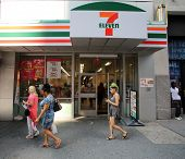 NEW YORK CITY - JULY 8: Pedestrians walk past a 7-Eleven convenience store in New York City, New York, on Monday, July 8, 2013.
