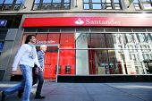 NEW YORK CITY - OCT 20 2013: Pedestrians walk past a branch of Santander Bank in Manhattan on Sunday, October 20, 2013.