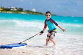 stock photo of boogie board  - Little boy on vacation having fun surfing on boogie board - JPG