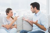 Couple having a serious argument on the couch at home in the living room