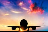 Airplane ready to take off. Silhouette of a big passenger or cargo aircraft, airline at sunset. Tran