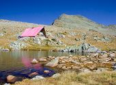 Cabin and a glacial lake up in national park Pirin