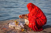 Indian woman performs morning pooja on sacred river Narmada ghats in Maheshwar, Madhya Pradesh, India. To Hindus Narmada is one of 5 holy rivers of India