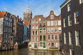 Streetview With Colorful Brick Houses And Dome Of St. Nicolas Church In Amsterdam