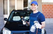 picture of gun shop  - Car body repairer holding a spray gun and a sheet of sandpaper - JPG
