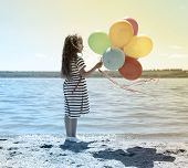 Beautiful little girl with colorful balloons on the beach