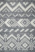 Closeup of knit fabric background with knitted grey and white geometric pattern