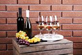 Bottles and glasses of wine, cheese and ripe grapes on box on brick wall background