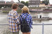 Young couple on the river bank in a European city (rear view) Romantic journey.