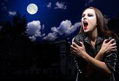 Vampire girl on night sky with moon