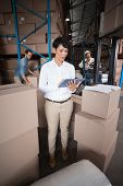Warehouse manager using her tablet pc in a large warehouse