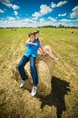 Young couple sitting on a hay stack