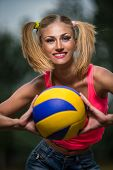Young happy sport woman giving you a volleyball ball