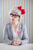 Funny woman with a grey hair wig holding heart shapes