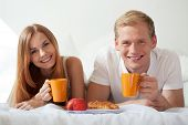 Smiling Couple Drinking Tea In Bed