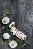 Button mushrooms and fresh herbs over black slate.  Overhead view food background.