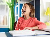 happy girl with home work in room laughing
