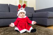 Baby girl with x mas dressing and sitting on carpet