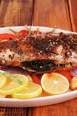 whole fried bass on plate, served with lemons and tomatoes