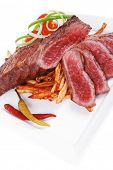 meat and potato : rare grilled beef steak served with pepper and tomato over plate isolated on white