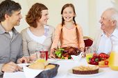 Portrait of happy family looking at joyful girl during Thanksgiving dinner