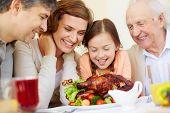 Portrait of joyful people looking at roasted turkey by festive table