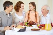Portrait of happy family members looking at cute girl by Thanksgiving table