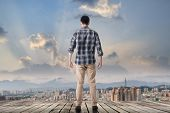 Asian man standing and looking the skyline of the city.