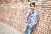 Cool fashion man in blue shirt and sunglasses sitting with his hand in pocket, smiling and looking a