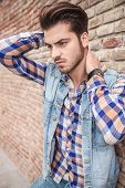 Side view of a young man leaning on a brick wall holding his hand on his neck, looking away from the