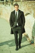 Full length picture of a elegant business man on a sidewalk near a brick wall holding his hands in p