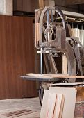 Old bandsaw cutting wood in wrorkshop
