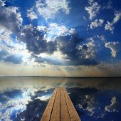 beautiful landscape with wooden pier on big lake and sky reflection