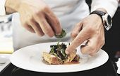 Chef is decorating delicious dish, motion blur on hands, toned image