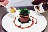 Chef is decorating tenderloin steak with sauce, motion blur on spoon, toned image