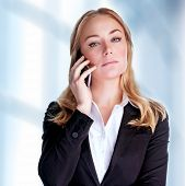 Portrait of attractive confident businesswoman speaking on phone in the office, communicate with bus