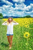 Joyful girl walking in sunflowers field, active lifestyle, agricultural landscape, enjoying blooming